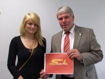 Bürgermeister Carl J. Lehrke überreicht Hannah Dezelske den Siegerpreis.