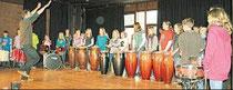 Der Musiker Bernd Lange dirigiert im KGS-Forum eine Schülergruppe beim Trommel-Workshop. (haz)