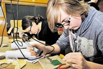 Feinarbeit: Die Schüler John Pierre (15) und Anna Lea (14) löten im KGS-Werkraum Platinen für die Radios, die der Technikkursus der Schule zusammen mit Holcim- Mitarbeitern baut. Brunhöber