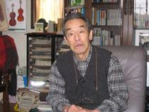 参納さん自宅にて。沖縄関係の本がたくさん並んでいる。