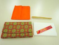 左上より時計まわりに)袱紗(ふくさ)表千家流:オレンジ色、茶席用扇子、懐紙と菓子切ようじ、袱紗ばさみ
