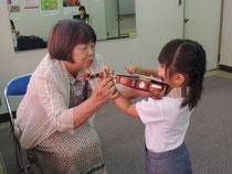 持ち運びが簡単で、どこでも弾けるというのがヴァイオリンの大きな特徴です。2~3歳では16分の1というもっとも小さな楽器を使い、「キラキラ星変奏曲」から始めます。ゴセックの「ガヴォット」が弾けるようになると意欲も芽生え、次にドヴォルザークの「ユーモレスク」やヴィヴァルディの「協奏曲」が目標となります。いろいろな曲が弾ける喜びとともに、スズキ・トーンといわれる美しい音を作ることも大切な目的です。研究科