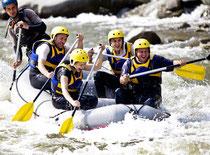 Fünf Personen mit Freude beim Wild-Water Rafting in einem Boot