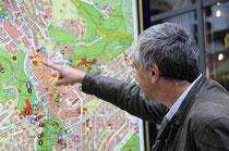 Ein Mann zeigt auf einer Straßenkarte, wo er hin möchte. Wo sein Ziel ist.