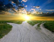 Weggabelung aus einem Feldweg in Richtung Sonnenaufgang