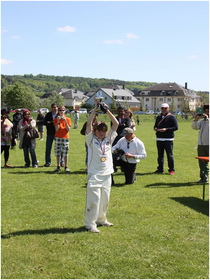 Victorious Swiss U11 captain Chris Langford receives the trophy