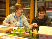 Ein Mitarbeiter des Montessori-Teams Münster mit einem Pädagogik-LK-Schüler einer Besuchergruppe