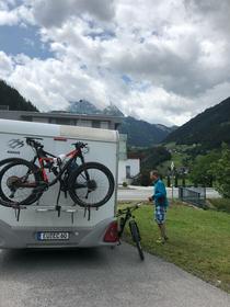 Fahrrad, Wohnmobil, Turnschuhe, Berge, kurze Hose, Euskirchen, Vanlife, on the road again, Mann steht vor Wohnmobil, Mayerhofen, Kennzeichen