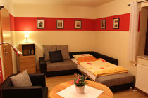 Wohnzimmer mit Aufbettung für eine Person