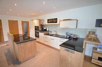 Eine große Küche mit hellen freundlichen Fronten kombiniert mit Eichen Nachbildung. Arbeitsfläche aus Granit Nero Assoluto poliert. Backrohr, Dampfgarer und Geschirrspüler erhöht eingebaut für ergonomisches Arbeiten,