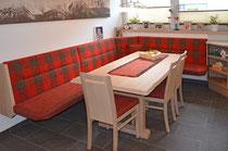 Eine frei schwebende, große Eckbank für einen störungsfreien Einstieg. Eine verlängerbare Tischplatte mit einer naturbelassenen Randform. Tisch und Sessel sind aus weißlich gebeizter Eiche gemacht.