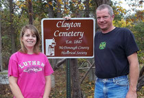 Lisa and Steve Hood accept a new sign from the McDonough County Historical Society marking the Clayton Cemetery which is on their property.