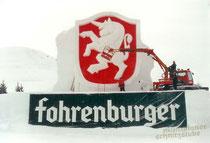 Schneeskulptur – Markenzeichen der Brauerei Fohrenburger – aus verdichtetem Schnee– Hintergrund mit Lebensmittelfarbe gefärbt
