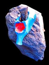 """""""Oberschenkelhals"""" / Werkverzeichnis 4.244 Gefertigt 2017 Ausgetrockneter Tierknochen gefunden am Mittelmeerstrand auf Fels mit Felsstückchen festgesteckt und mit blauer und roter Farbe versehen. Maße b 9,0 cm * t 8,0 cm * h 24,0 cm"""