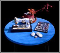 """""""Arrangement"""" Ca. 2014 - Blau lackierter Tisch, weiß gesprühte Nähmaschine mit Rost, Tonschale mit Kies und bepflanzten Betonstein, drei weiße Kieselsteine und sieben mit Sprühfarbe bemalte Holzlatten. Durchm. 120 cm / Nachträge WVZ"""