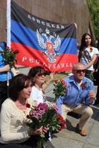Menschen mit Blumen und Sankt-Georgs-Band lassen sich vor russischer Fahne fotografieren. Foto: Helga Karl am 9.5.2015 Sowj. Ehrenmal Berlin