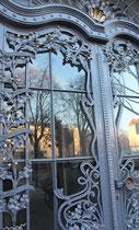 Nachmittagssonne spiegelt sich im Glas einer Haustür voll schmiedeeisernen Ranken. Friedenau. Foto: Helga Karl