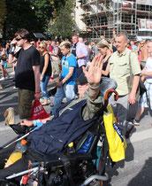 """Älterer Mann im Rollstuhl mit Antrieb winkt. """"Zug der Liebe"""" am 25.7.2015 Berlin. Foto: Helga Karl"""