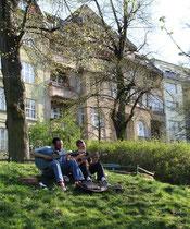 Zwei Musiker sitzen auf dem Rasen. Wohnhäuser am Lietzensee. Foto: Helga Karl