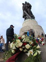 Menschen und viele Blumengebinde, niedergelegt an den Stufen beim Denkmal des Soldaten mit Kind der Roten Armee. 9.Mai, Sowjetisches Ehrenmal Treptow Berlin. Foto: Helga Karl