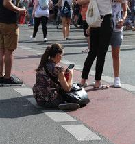 """Frau sitztauf der Strasse und tippt in ihr Handy. Wartender """"Zug der Liebe"""" Berlin. Foto: Helga Karl"""