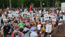 Viele Menschen mit Blumen in der Hand, Sankt-Georgs-Band an der Kleidung, halten Plakate hoch mit Fotos ihrer Angehörigen der Roten Armee. Foto: Helga Karl 9.5.2015