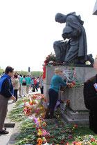 Ein Frau legt Blumen nieder. Denkmal Knieender Soldat, umgeben von Blumen. Sowj. Ehrenmal. Foto: Helga Karl am 5.Mai 2015