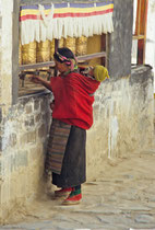 Woman with a baby on her back rolling the prayer wheels, Tashilhuenpo Monastery, Shigatse, Tibet 1993