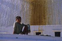 Young boy sitting on Boudhanath stupa, Nepal 1989