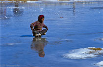 Little boy playing on a frozen pond in Old Tingri, Tibet 1993