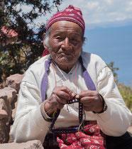 Alter Mann strickt  am Titicacasee ( Lago Titicaca )