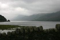 Eilean Donan Castle mit Blick auf Loch Duich und die herannahenden Regenwolken.