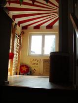 Kinderzimmer mit rot-weißer Zirkusdecke