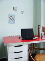 Schreibtisch mit roter Platte vor jadegrüner Wand