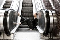 Balletttänzerin post auf Rolltreppenstufen