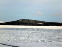 """Blick auf die Insel Päijätsalo und das Ferienhausgebiet mit dem Sunny Mökki Sysmä sowie dem """"Berg"""" mit Aussichtsturm im Winter."""