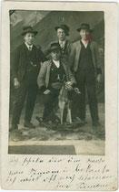 """Jungmänner u.a. in grauen Jankern aus Tuxer Steinschafwolle mit schwarzem Besatz, darunter einer """"aus Jux und Tollerei"""" auf einem zweckentfremdete Schaukelpferd sitzend. Gelatinesilberabzug 9 x 14 cm ohne Impressum, um 1925.  Inv.-Nr. vu914gs00876"""