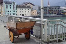 Handwagen mit nachträglich erhöhter Bordwand und Reinigungswerkzeug für Straßenkehrer auf der Innbrücke in der Bezirkshauptstadt Kufstein, Tirol. Digitalphoto; © Johann G. Mairhofer 2013.  Inv.-Nr. 1DSC05647