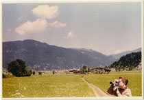 Junger Schmalfilmamateur beim Drehen einer Szenerie auf einem Spaziergang in Kirchdorf, Bezirk Kitzbühel, Tirol. Baryt-Farbphotopapier 7,5 x 11,0 cm mit weißem Schmuckrand, wohl Amateuraufnahme um 1960. Inv.-Nr. vu7511fph00001
