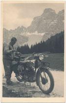 Tiroler Alpinist mit Kletterseil am Motorrad der Marke Puch 250 S Bj. 1932 wohl in Selva di Cadore und der Monte Pelmo (3.168 m s.l.m.) im Pelmostock der Dolomiten. Gelatinesilberabzug 9 x 14 cm (Amateuraufnahme) um 1935.  Inv.-Nr. vu914gs01197