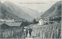 Bergtouristen in Gschnitz auf der von Flechtzäunen gesäumten Gschnitztalstraße. Lichtdruck 9 x 14 cm; Impressum: K(arl). Redlich, Innsbruck um 1910.  Inv.-Nr. vu914ld00030