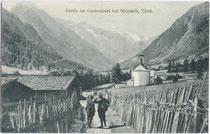 Bergtouristen in Gschnitz unterwegs auf der von Flechtzäunen gesäumten Gschnitztalstraße. Lichtdruck 9 x 14 cm; Impressum: K(arl). Redlich, Innsbruck um 1910.  Inv.-Nr. vu914ld00030