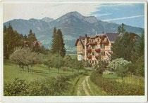 """Hotel """"Maximilian"""" in Igls, Stadtgemeinde Innsbruck mit Nockspitze in den Stubaier Alpen. Farbautotypie 10 x 15 cm; Impressum: Verlag Preiss & Co., München um 1925.  Inv.-Nr. vu105fat00030."""