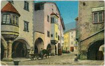 Lastfuhrwerk beim Haus mit Runderker Lauben Nr. 8 von 1599 in Neumarkt an der Etsch im Bozner Unterland. Photochromdruck 9 x 14 cm; Impressum: Joh(ann). F(ilibert). Amonn 1914.  Inv.-Nr. vu914pcd00304