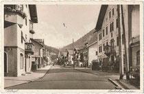 """Bahnhofstraße in Wörgl, Bzk. Kufstein, Tirol mit dem Gasthof """"zur Rose"""" (heute Wohn-/Geschäftshaus). Heliogravüre 9 x 14 cm; Verlag Danack's Nachf. Karl Bauer, Hauptplatz (heute Andreas-Hofer-Platz) 4, Wörgl um 1935.  Inv.-Nr. vu914hg00068"""