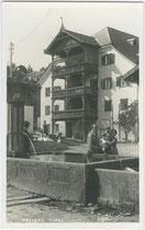 Ansitz Waidburg - heute darin u.a. das Gemeindeamt – mit mehrgeschoßiger offener Veranda und Dorfbrunnen in Natters, Bzk. Innsbruck Land, Tirol. Gelatinesilberabzug 9 x 14 cm; Impressum: A(lfred) Stockhammer, Hall in Tirol 1927.  Inv.-Nr. vu914gs00370