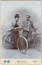 Paar mit Fahrrädern in zeitgenössischer Radsportkleidung. Gelatinesilberabzug auf Untersatzkarton   16,6 x 10,8 cm. Impressum: K. u. K. Kammerfotograf Frid(olin). Arnold, Landhausstraße (heute Meraner Straße) 7, Innsbruck nach 1896. Inv.-Nr. vuCAB-00052
