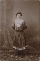 Junge Dame im Turnkostüm vor gemalter Hintergrundkulisse des Ateliers. Gelatinesilberabzug 9 x 14 cm. Impressum: Max Ketzler, Heiliggeiststraße 9, Innsbruck um 1905.  Inv.-Nr. vu914gs00859