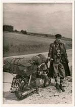 Junger Mann in zeitgenössischer Motorradkleidung (z.B. Ledermantel, Knickerbocker, Baskenmütze) und eine PUCH mit aufgeladener Reise- und Campingausrüstung. Gelatinesilberabzug 9 x 12 cm (wohl Amateuraufnahme ) um 1960.  Inv.-Nr. vu912gs00025