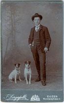 Verbindungsstudent in Hemd mit Vatermörder (Stehkragen), dreiteiligem Anzug mit Bierzipf, Fritzstock und Hut mit Hunden. Gelatinesilberabzug auf Untersatzkarton 10,6 x 6,8 cm (Visit-Format). F. Largajolli, Bozen um 1910.  Inv.-Nr. vuVIS-00110